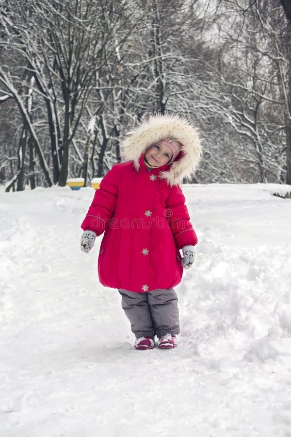 La pequeña muchacha linda en una capilla roja brillante de la chaqueta y de la piel que se coloca en un invierno parquea imágenes de archivo libres de regalías