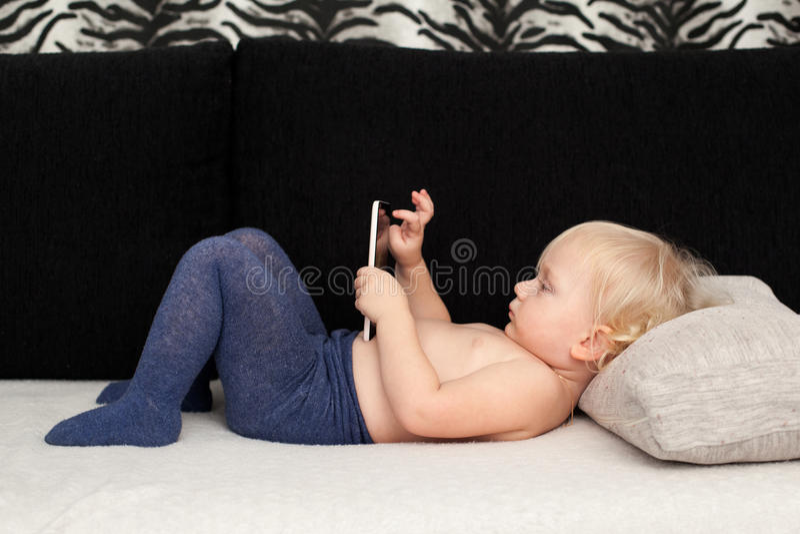 La pequeña muchacha linda está jugando con un smartphone fotos de archivo libres de regalías