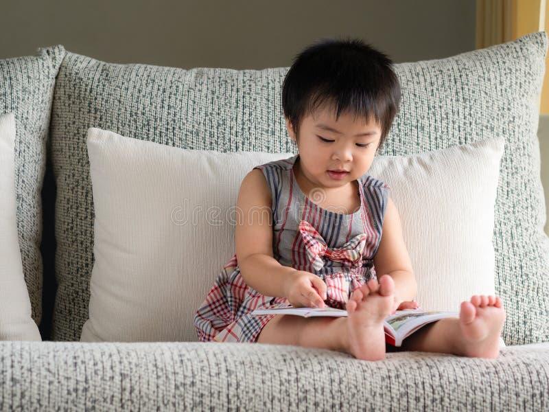 La pequeña muchacha linda feliz está leyendo el libro en el sofá blanco Ed imagen de archivo