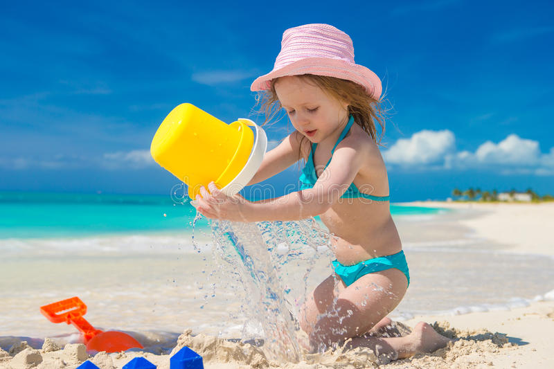 La pequeña muchacha linda que juega con la playa juega durante imagen de archivo libre de regalías