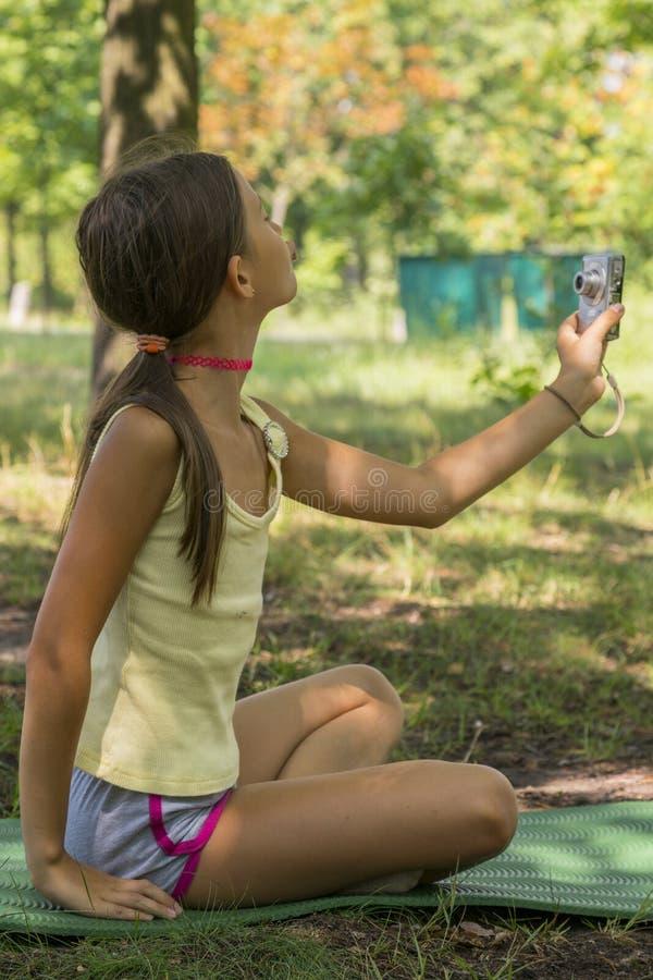 La pequeña muchacha linda que sostiene la cámara disponible y toma una imagen con el selfie tirado en parque muchacha de ocho año fotografía de archivo libre de regalías