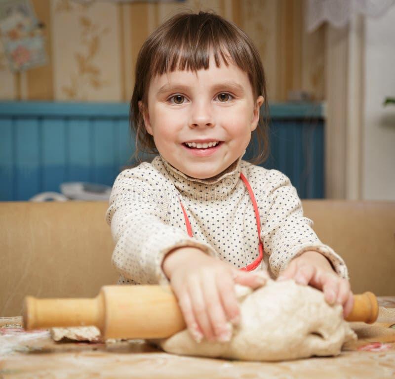 La pequeña muchacha linda rueda la pasta foto de archivo libre de regalías