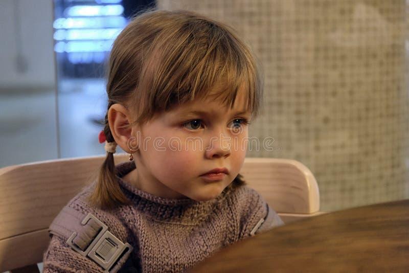 La pequeña muchacha linda sobre algo pensó imagenes de archivo