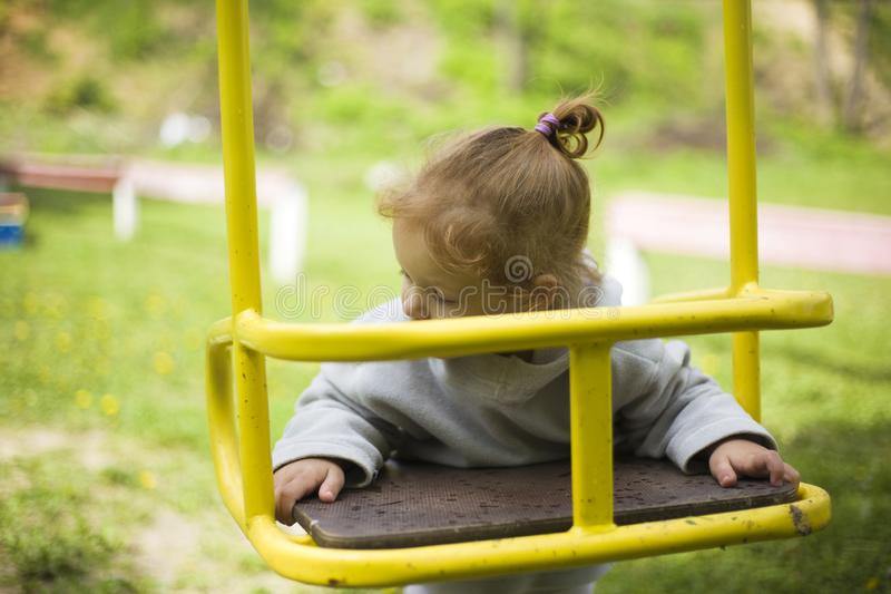 La pequeña muchacha pelirroja hermosa colgó en un oscilación, bebé juega en un oscilación en el patio fotografía de archivo libre de regalías