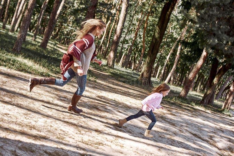 La pequeña muchacha rizada feliz, elegante está corriendo con su madre hermosa en bosque fotografía de archivo libre de regalías