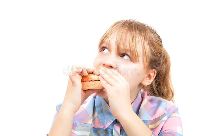La pequeña muchacha rubia come la hamburguesa imágenes de archivo libres de regalías