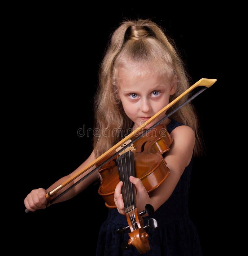 La pequeña muchacha rubia feliz aprende tocar el violín aislado en negro imagen de archivo