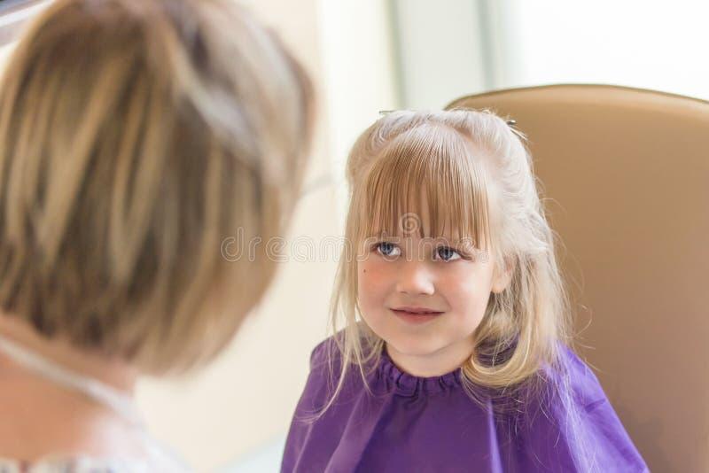 La pequeña muchacha rubia linda sonríe y mira al peluquero durante proceso del corte de pelo fotografía de archivo libre de regalías