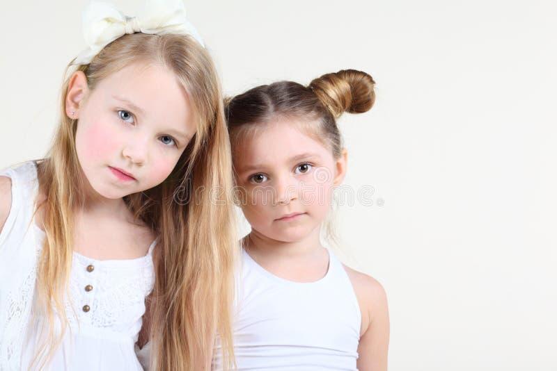 La pequeña muchacha seria dos en la ropa blanca mira la cámara fotografía de archivo libre de regalías