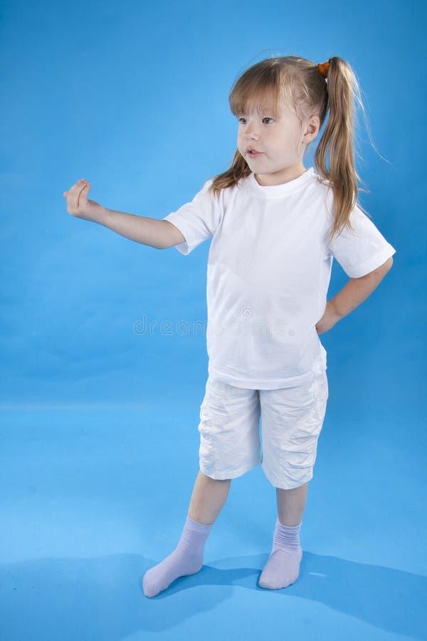 La pequeña muchacha seria está presentando aisló en azul fotos de archivo libres de regalías