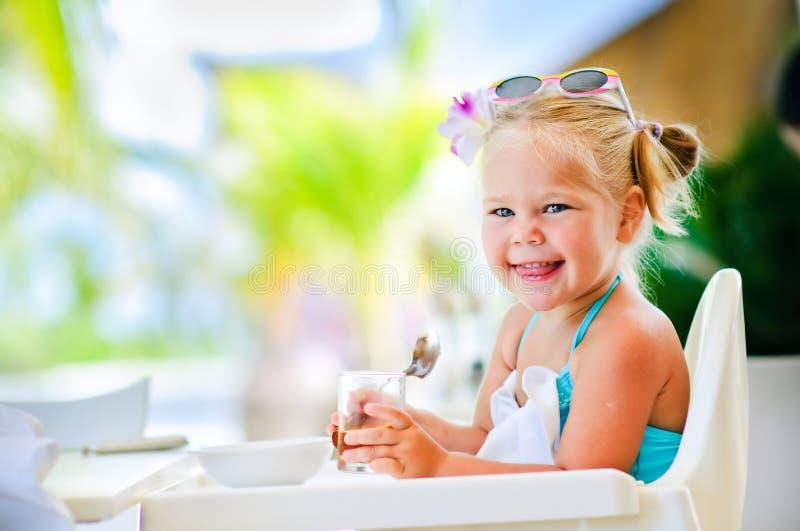 La pequeña muchacha sonriente desayuna imagen de archivo