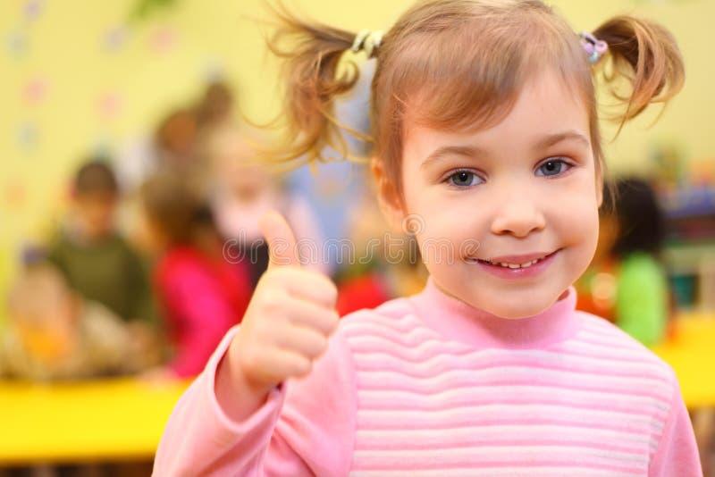 La pequeña muchacha sonriente en jardín de la infancia muestra OK imagen de archivo libre de regalías