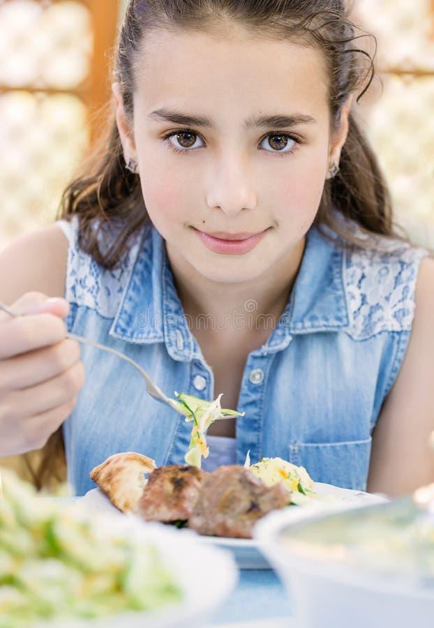 La pequeña muchacha sonriente hermosa con placer come el kebab a al aire libre fotos de archivo