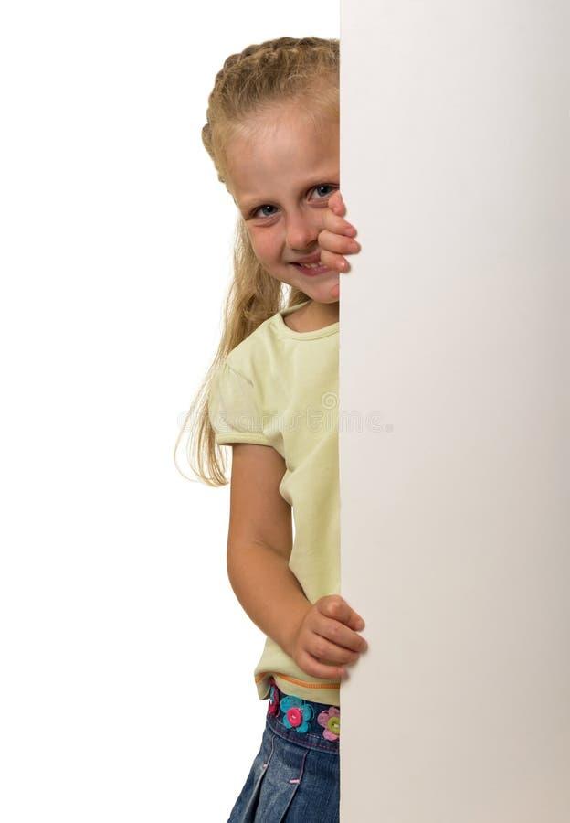 La pequeña muchacha sonriente mira a escondidas hacia fuera de detrás la bandera, aislada en blanco foto de archivo