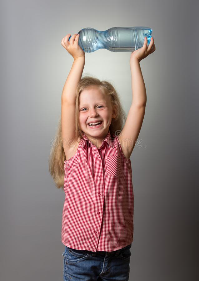 La pequeña muchacha sonriente sostiene la botella de agua sobre su cabeza en gris imagen de archivo