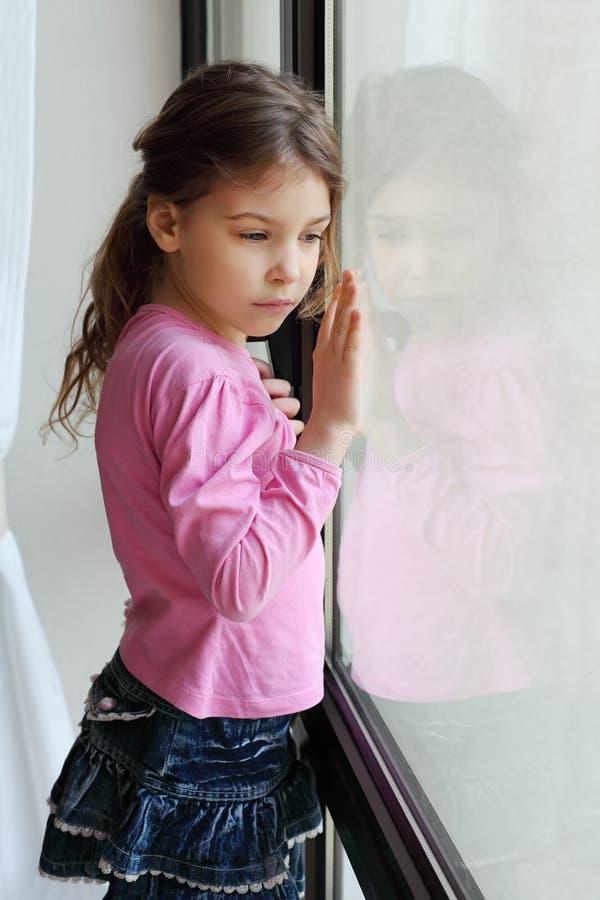 La pequeña muchacha triste mira hacia fuera la ventana fotografía de archivo