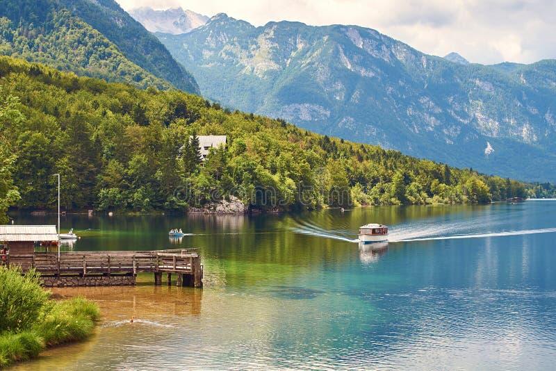 La pequeña nave llega al muelle de madera el lago Bohinj imagen de archivo libre de regalías