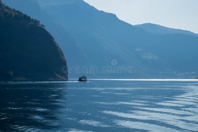 La pequeña nave navega en agua azul con mountais grandes Paisaje de Noruega, travesía del fiordo fotografía de archivo libre de regalías