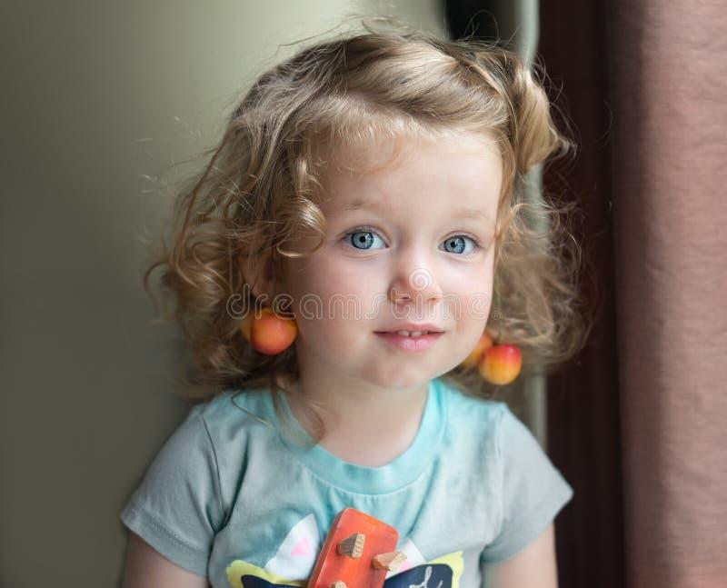 La pequeña niña pequeña caucásica rubia adorable del pelo rizado con los ojos azules y con una cereza como pendientes está mirand foto de archivo