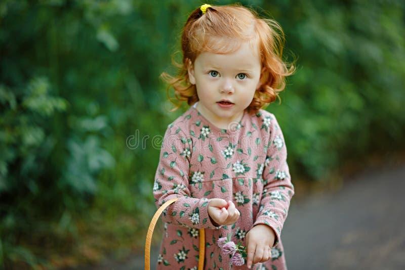 La pequeña niña pelirroja hermosa mira seriamente, verano imagenes de archivo