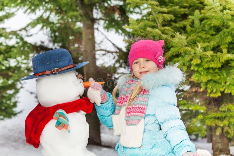 La pequeña niña puso la zanahoria que hacía el muñeco de nieve fotos de archivo libres de regalías
