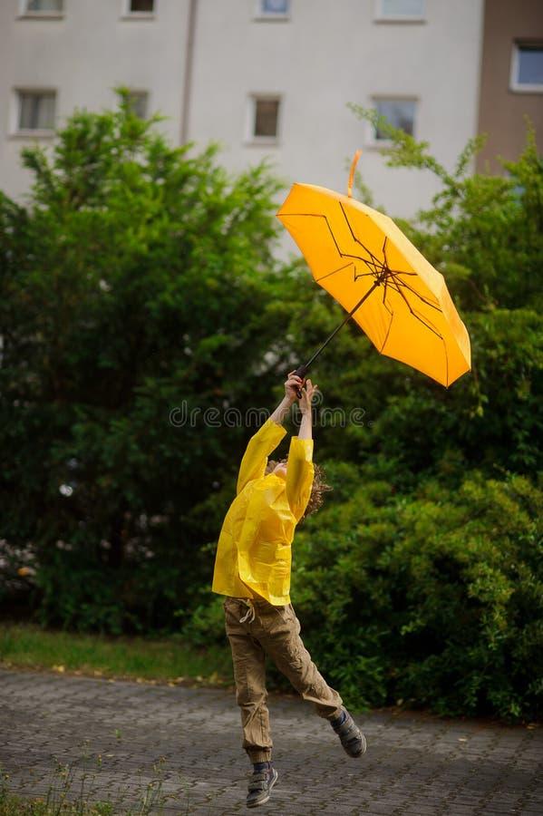 La pequeña persona en un impermeable amarillo brillante vuela sobre la tierra con un paraguas a disposición imagen de archivo libre de regalías