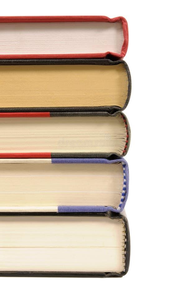 La pequeña pila de libro encuadernado reserva en el fondo blanco, vertical fotografía de archivo libre de regalías