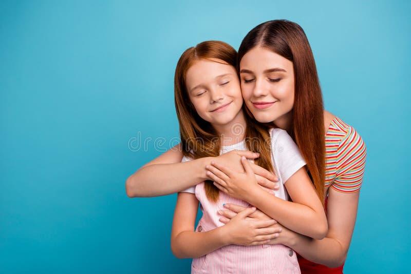 La pequeña señora astuta bonita y su mamá disfrutan de regreso al hogar después de fondo azul aislado de la ropa casual del desga imagen de archivo libre de regalías