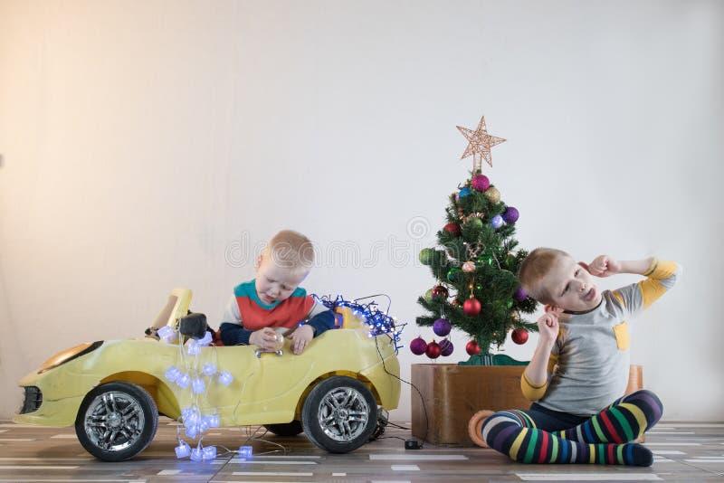 La pequeña sonrisa divertida embroma la conducción del coche del juguete con el árbol de navidad El niño feliz en la moda del col imagen de archivo libre de regalías