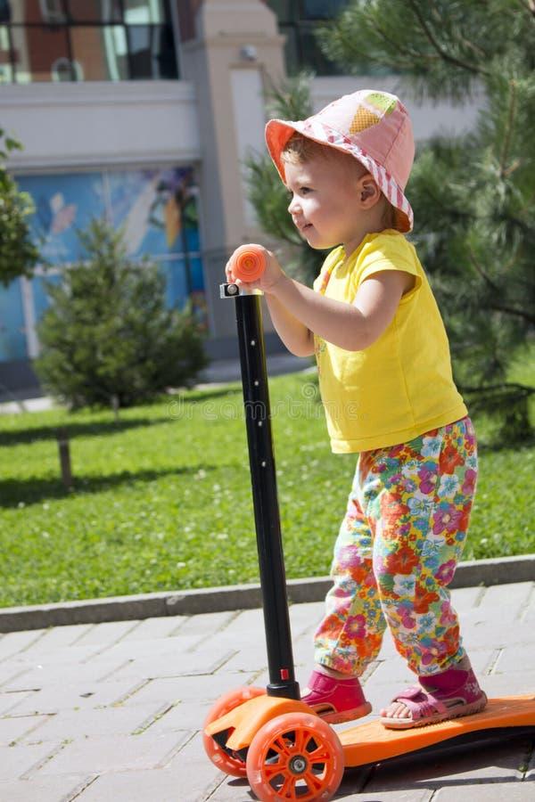 La pequeña vespa linda en la ciudad, niños del montar a caballo de la niña pequeña se divierte vertical fotos de archivo libres de regalías