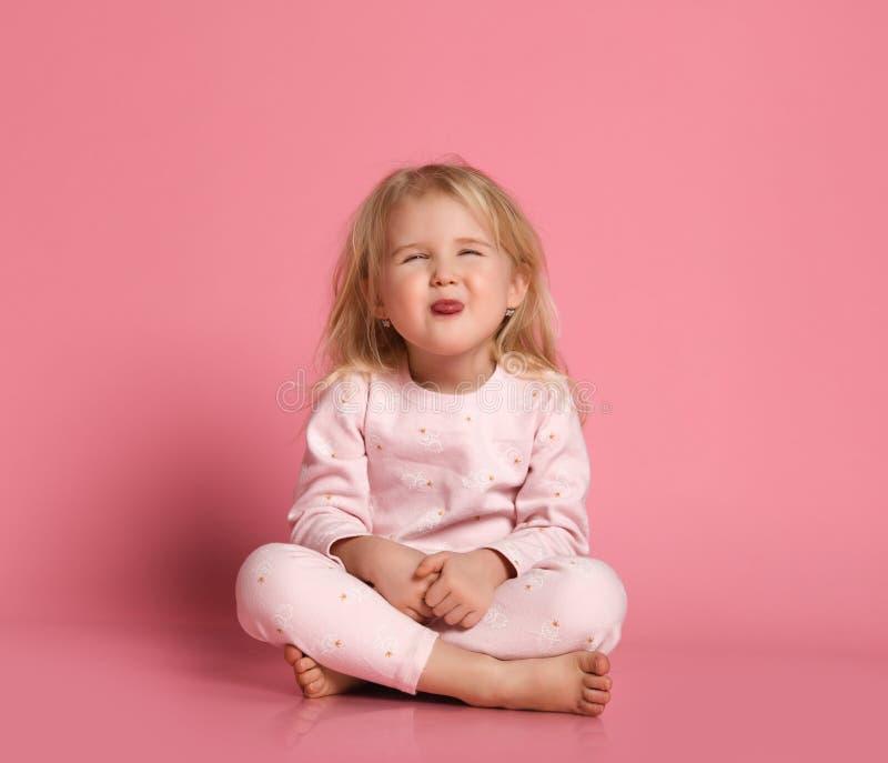 La peque?a muchacha linda alegre en pijamas se sienta en el piso en fondo rosado imagen de archivo libre de regalías