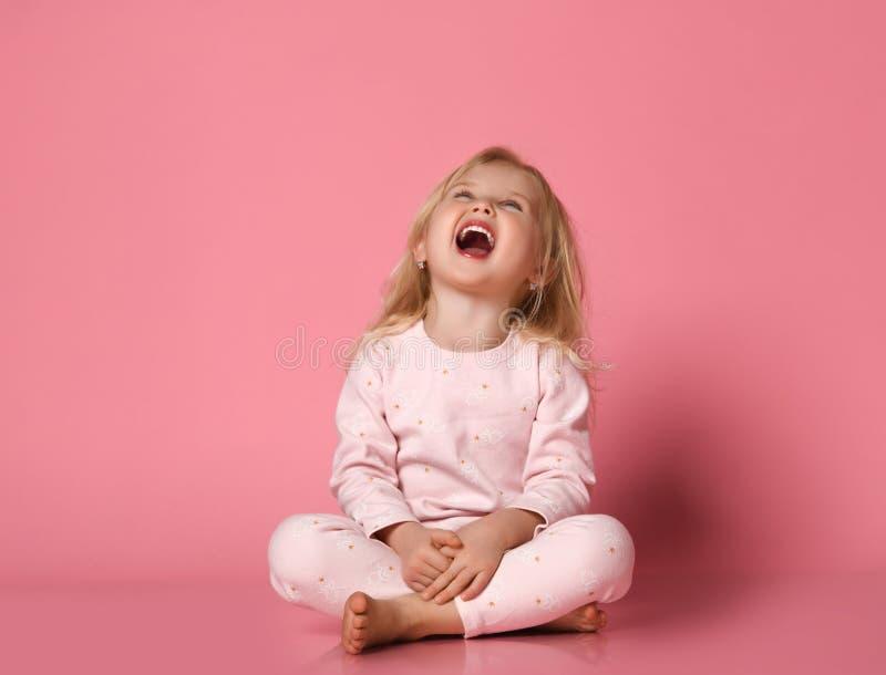 La peque?a muchacha linda alegre en pijamas se sienta en el piso en fondo rosado foto de archivo libre de regalías