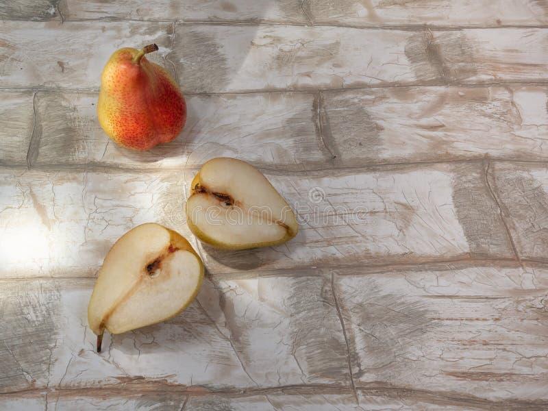 La pera cortó en 2 mitades en un ladrillo de madera de la imitación del fondo fotos de archivo libres de regalías