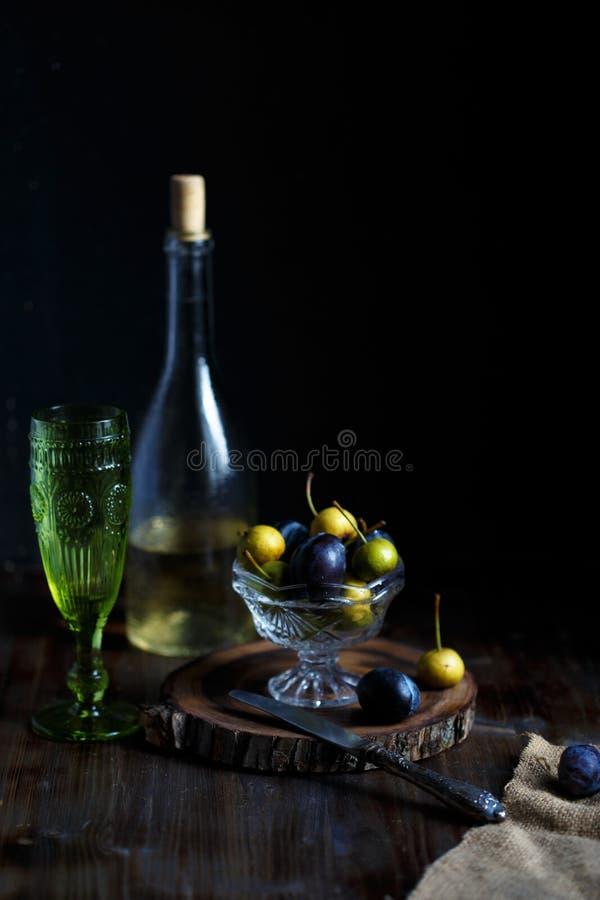 La pera y el ciruelo salvajes en un bol de vidrio, un vidrio y una botella de pera hecha en casa wine en un fondo cercano de made imágenes de archivo libres de regalías