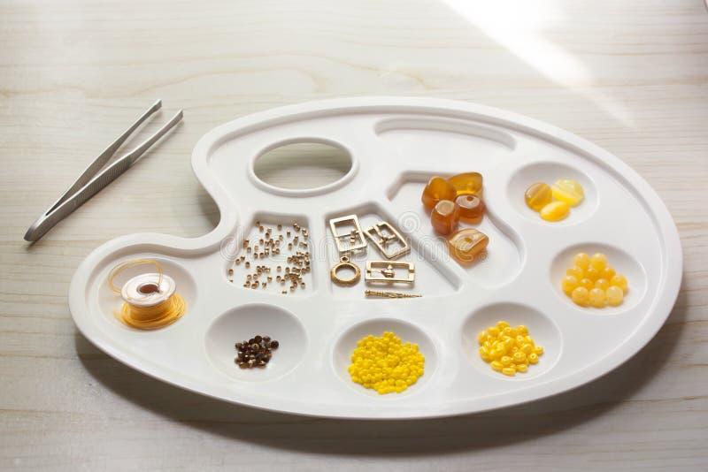 La perle et les composants jaunissent, orange pour des bijoux faisant sur la palette blanche photo libre de droits