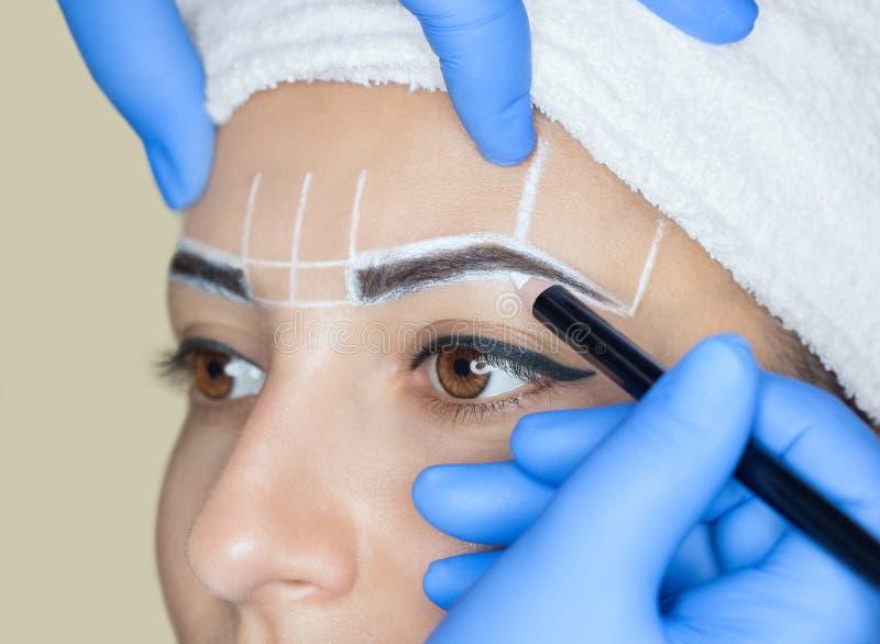 La permanente compensa las cejas de la mujer hermosa con las frentes gruesas en salón de belleza fotos de archivo libres de regalías