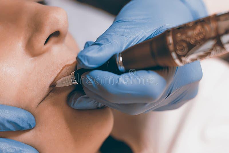 La permanente compone Cosmetologist que aplica maquillaje permanente en el li imágenes de archivo libres de regalías