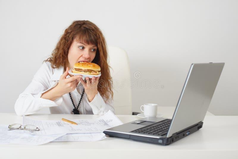 La persona all'ufficio sul posto di lavoro mangia un hamburger fotografia stock libera da diritti