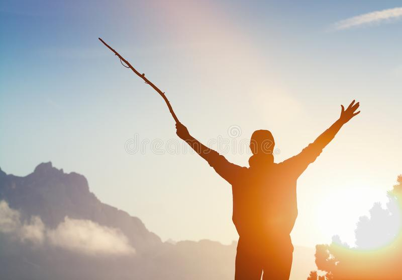 La persona anonima sta al tramonto sulla cima di una montagna con le armi alzate fotografie stock libere da diritti