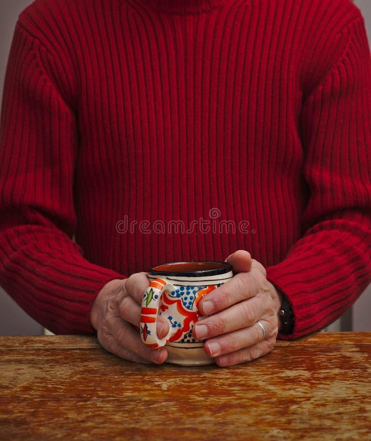 La persona calentando las manos alrededor de la taza foto de archivo