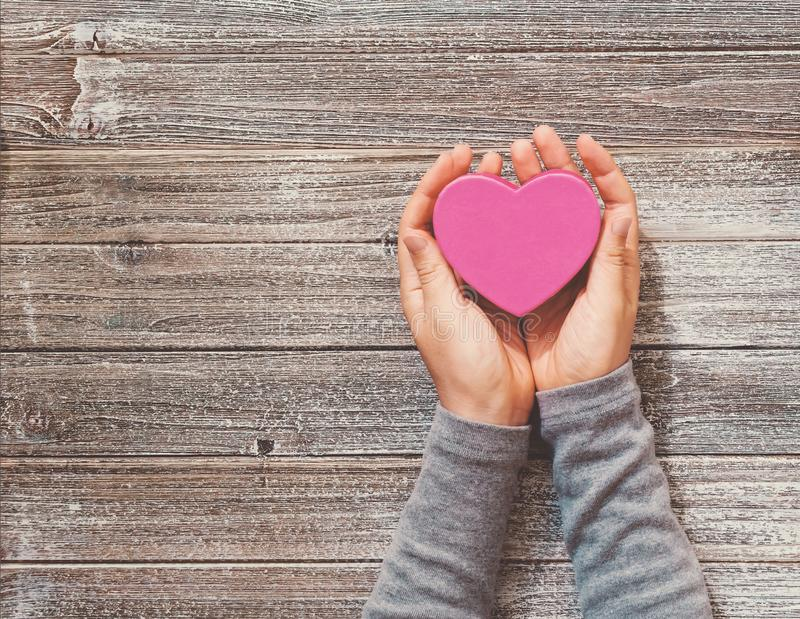 La persona che tiene il cuore ha modellato la scatola in sue mani immagine stock
