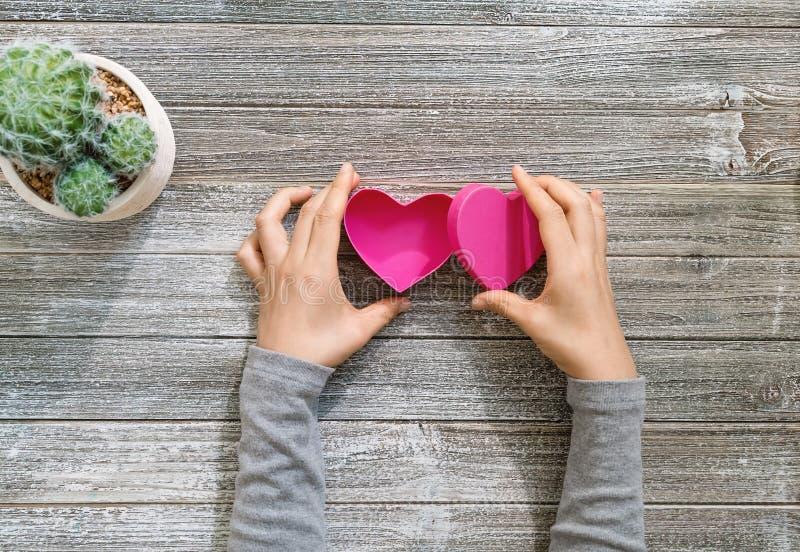 La persona che tiene il cuore ha modellato la scatola in sue mani fotografia stock libera da diritti