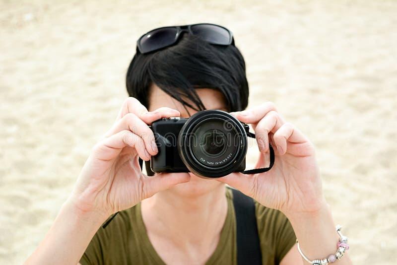 La persona con la piccola macchina fotografica nera fotografie stock