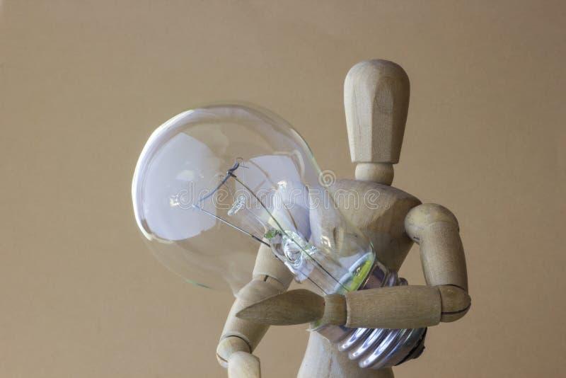 La persona de madera sostiene el bulbo eléctrico disponible imagenes de archivo