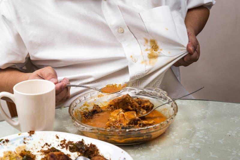 La persona derramó accidentalmente la mancha del curry sobre la camisa blanca foto de archivo