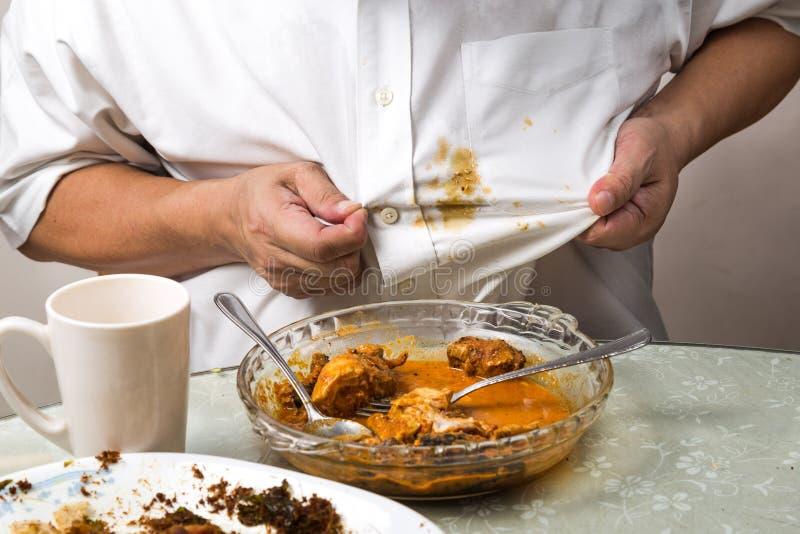 La persona derramó accidentalmente la mancha del curry sobre la camisa blanca fotografía de archivo libre de regalías