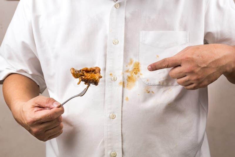 La persona derramó accidentalmente la mancha del curry sobre la camisa blanca fotografía de archivo