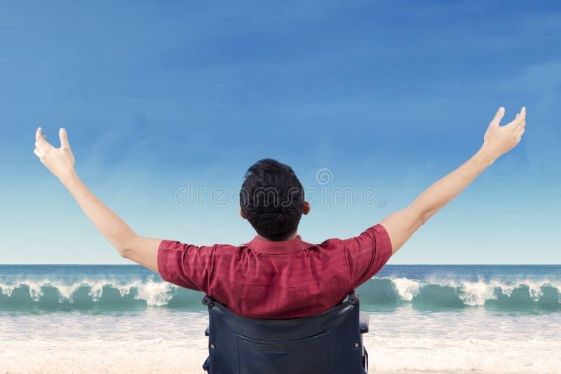 La persona discapacitada disfruta de la libertad en la costa foto de archivo