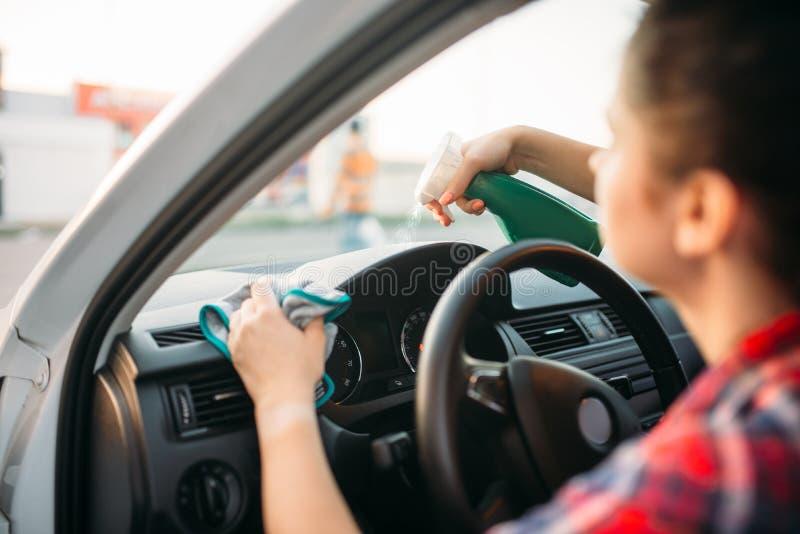 La persona femenina pule el tablero de instrumentos del coche foto de archivo libre de regalías