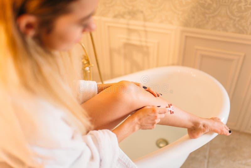 La persona femminile rade le gambe in bagno immagini stock libere da diritti